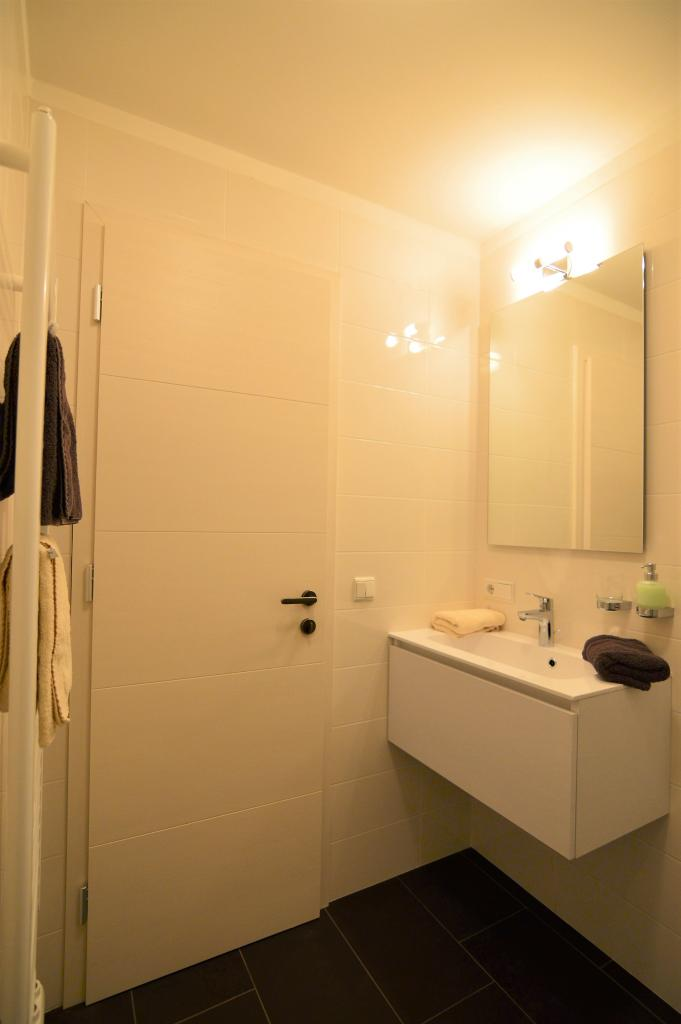 Das Bad Ist Klassisch Bis An Die Decke Gefliest. An Den Wänden Sind  Cremefarbene Glänzenden Fliesen, Der Boden Ist Aus Purpurfarbenen Schiefer